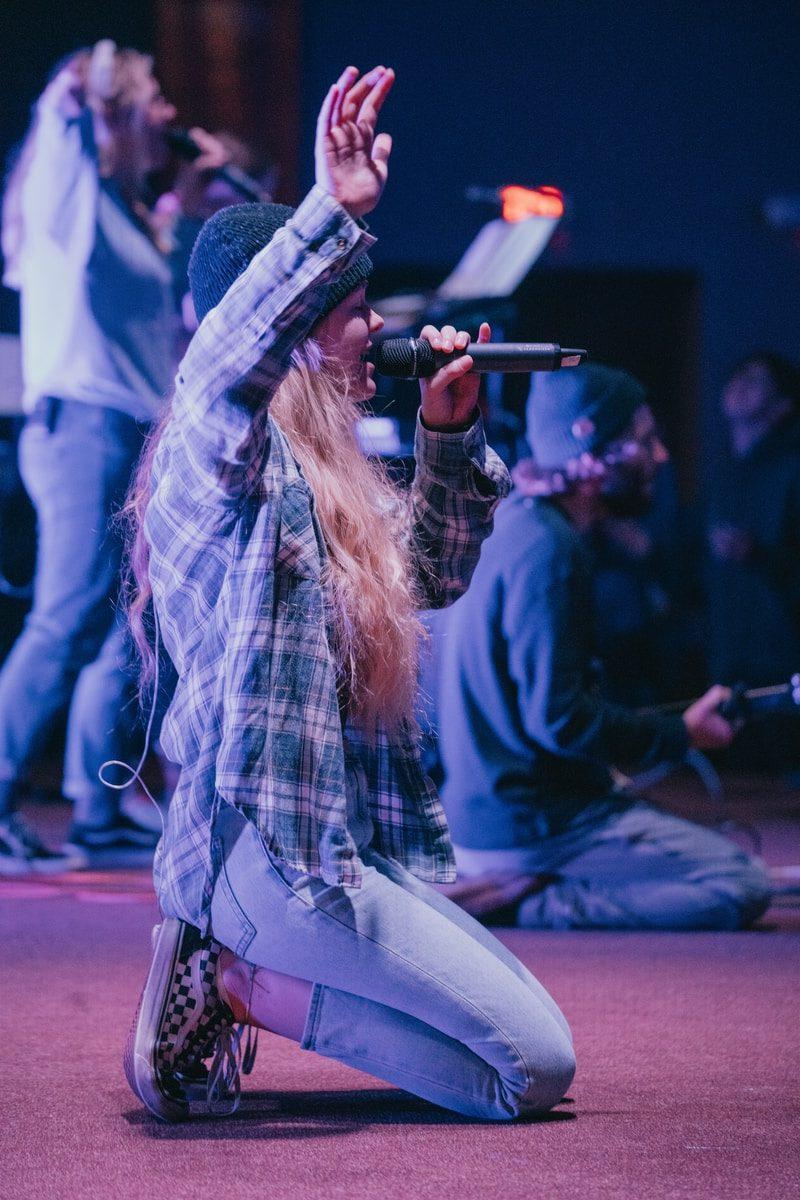 kneeling woman while singing